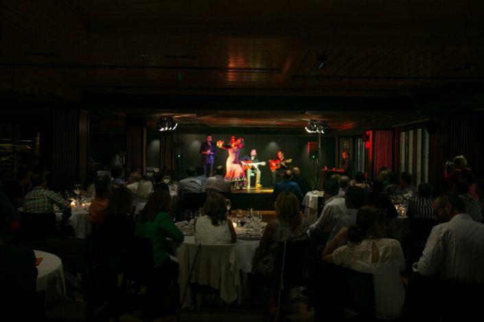 Asistentes a evento viendo espectáculo flamenco